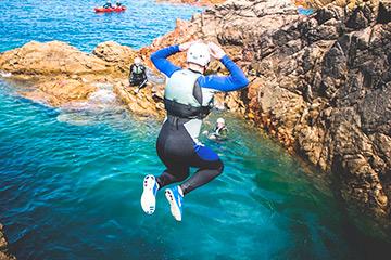 Persona saltando al agua desde un barranco coasteering barranquismo