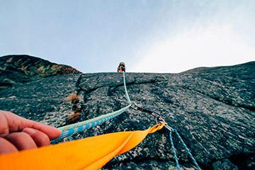 Persona escalando en roca con rápel y cuerda